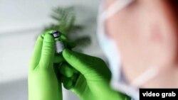 Një punonjës shëndetësor mban në duar dozën e vaksinës së Pfizerit.
