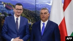 Polish Prime Minister Mateusz Morawiecki (left) and Hungarian Prime Minister Viktor Orban pose ahead of a press conference in Brussels on September 24.