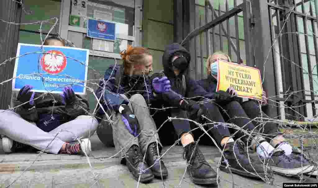 Activists on August 23 behind coils of barbed wire at the headquarters of Poland's Border Guards to protest the stance taken by the authorities.