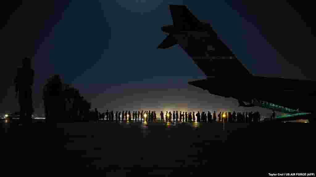 АҚШ әскери ұшағының борт қызметкерлері эвакуация тізіміндегі азаматтарды ұшаққа отырғызуға дайындап жатыр. Кабул әуежайы, 22 тамыз 2021 жыл.