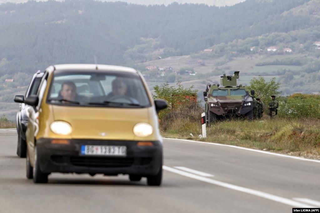 Automjete duke lëvizur nëpër një rrugë, pranë një autoblinde të ushtrisë serbe, në Rudnicë. (27 shtator)