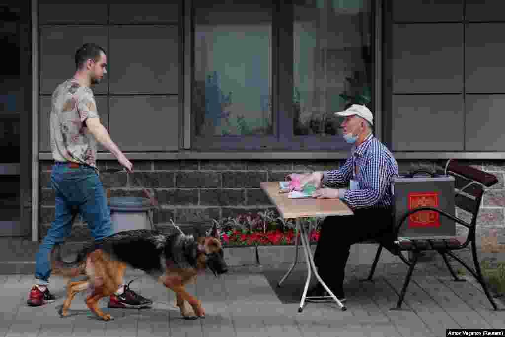 Un alegător din Sankt-Petersburg a venit împreună cu câinele său la o secție de votare deschisă în aer liber.
