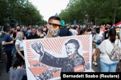 Акция протеста в Будапеште против строительства филиала китайского вуза. Демонстрант держит плакат, на котором премьер Виктор Орбан изображен в виде Мао