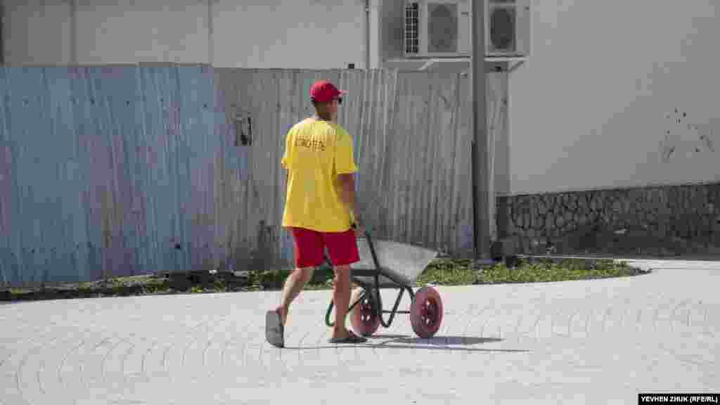 Молода людина в формі пляжного рятувальника везе кудись візок