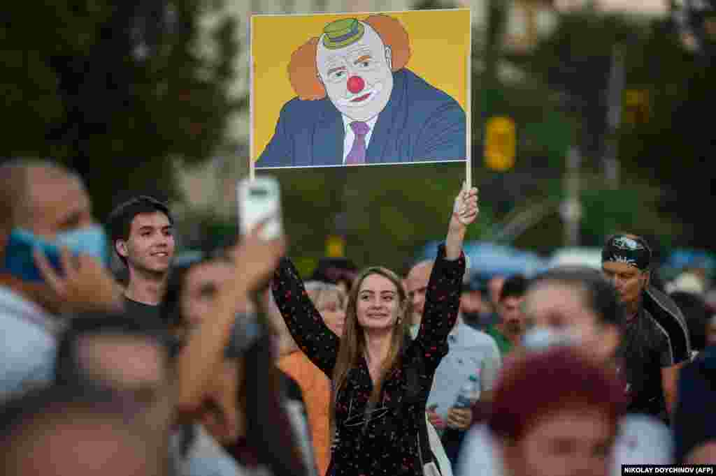 A woman holds a placard depicting Bulgarian Prime Minister Boyko Borisov as a clown during an anti-government protest in Sofia on July 20. (AFP/Nikolay Doychinov)