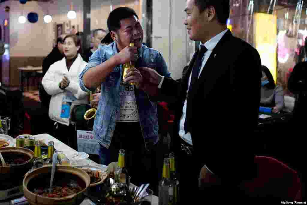 Egy férfi fogával nyit ki egy sörösüveget egy utcai étteremben 2020. december 11-én, Vuhanban.