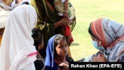 PAKISTAN -- Residents of Ibrahim Hyderi receive medical treatment at a medical camp set up by the Raghib Social Welfare Organization, after new cases of COVID-19 were reported in Karachi, February 16, 2021