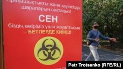 Человек в маске у баннера с информацией о коронавирусной инфекции.