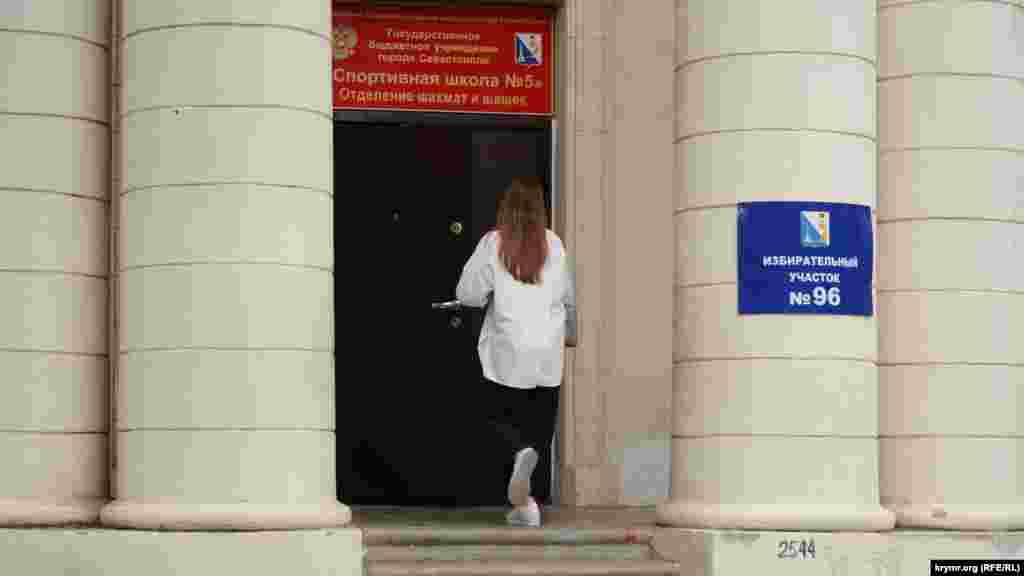 Молода жінка заходить на виборчу дільницю № 96, розташовану в приміщенні спортивної школи в Севастополі, 18 вересня