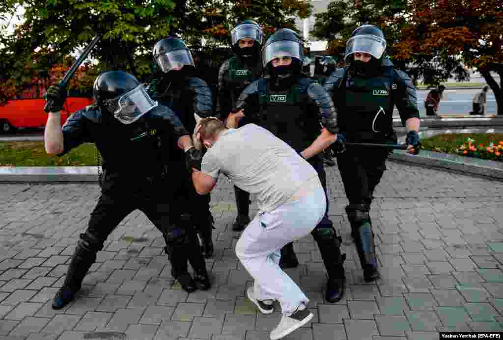 A demonstrator is grabbed by riot policemen in Minsk.