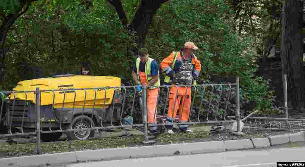 С помощью отбойного молотка демонтируется железный заборчик у сквера Мира
