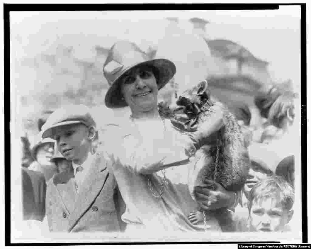 18 апреля 1927 года. Первая леди Грейс Кулидж, жена 30-го президента Калвина Кулиджа, во время Пасхального обеда в Белом доме показывает детям домашнего любимца семьи – енота Ребекку