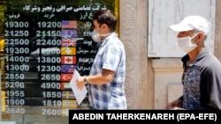 An Iranian man checks currency rates as he walks past an exchange bureau in Tehran. June 22, 2020.