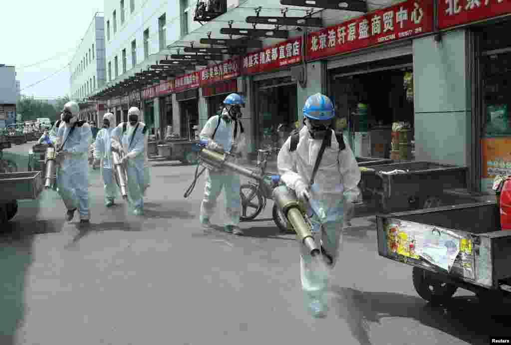 Добровольці з команди рятівників Blue Sky в захисних костюмах дезінфікують гуртовий ринок Югжуанг (Yuegezhuang) після нових випадків захворювання коронавірусом (COVID-19) в Пекіні, Китай