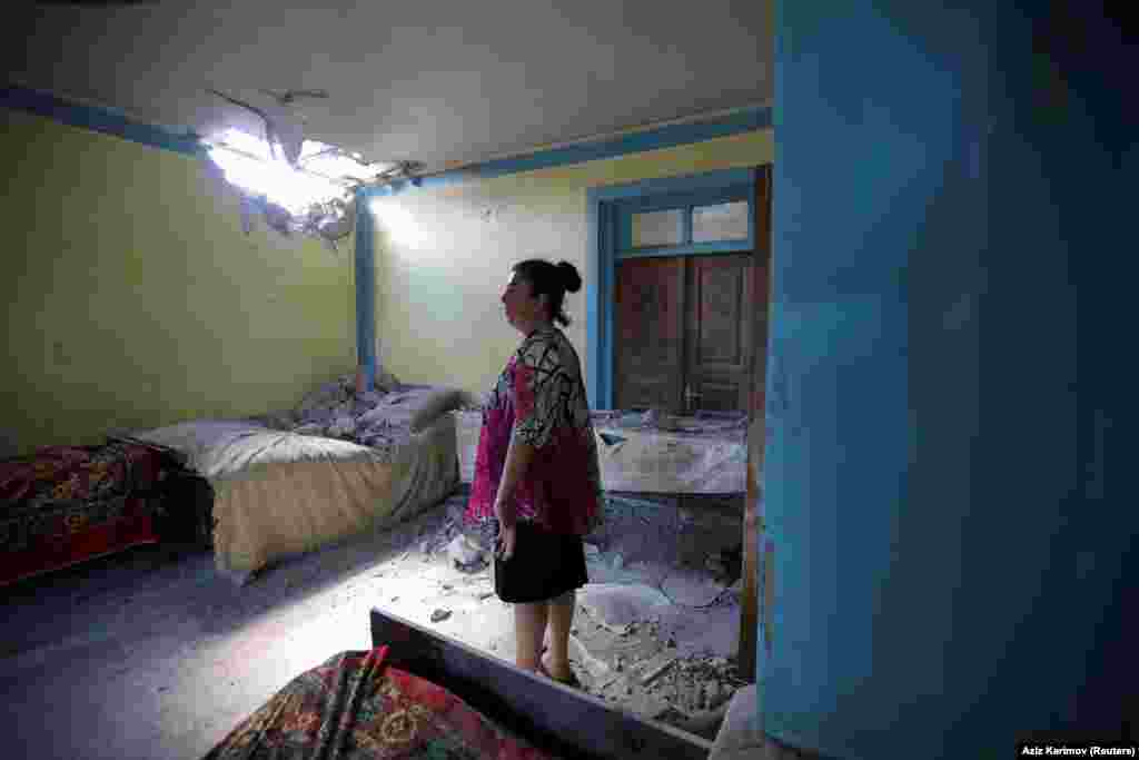 A woman in the Azerbaijani village of Dondar Gushchu inspects damage to her home caused by an Armenian shell.