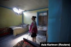 В азербайджанському селі Дондар Гущу жінка оглядає пошкодження її будинку, заподіяні вірменським снарядом