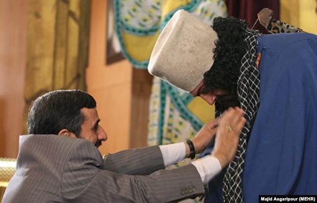 محمود احمدینژاد در حال انداختن چفیه بر گردن «سرباز هخامنشی» در نمایشگاه منشور کوروش در شهریور ۸۹