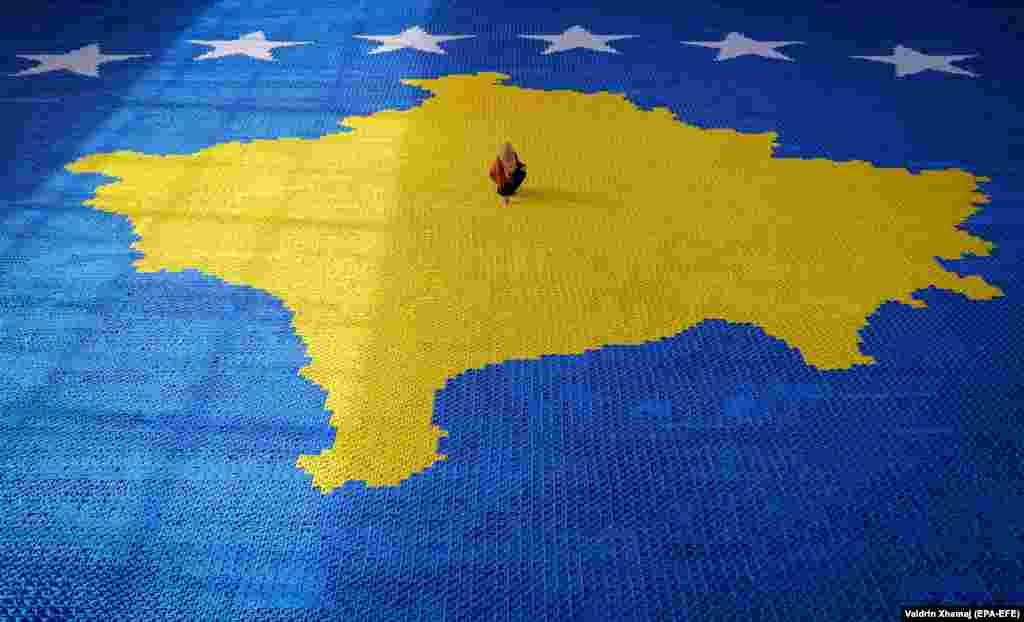 Kosovar artist Arbnora Fejza Idrizi gives the finishing touches to her origami mosaic showing Kosovo's national flag in the town of Skenderaj on February 10. (epa-EFE/Valdrin Xhemaj)