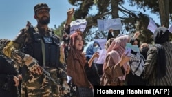 A Taliban fighter stands guard as Afghan women shout slogans during a protest rally near the Pakistani Embassy in Kabul on September 7.