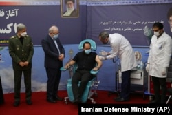 A son of slain scientist Mohsen Fakhrizadeh receives a Fakhra coronavirus vaccine as Defense Minister Gen. Amir Hatami (left) and Health Minister Saeed Namaki (2nd left) look on at a staged event in Tehran on March 16.