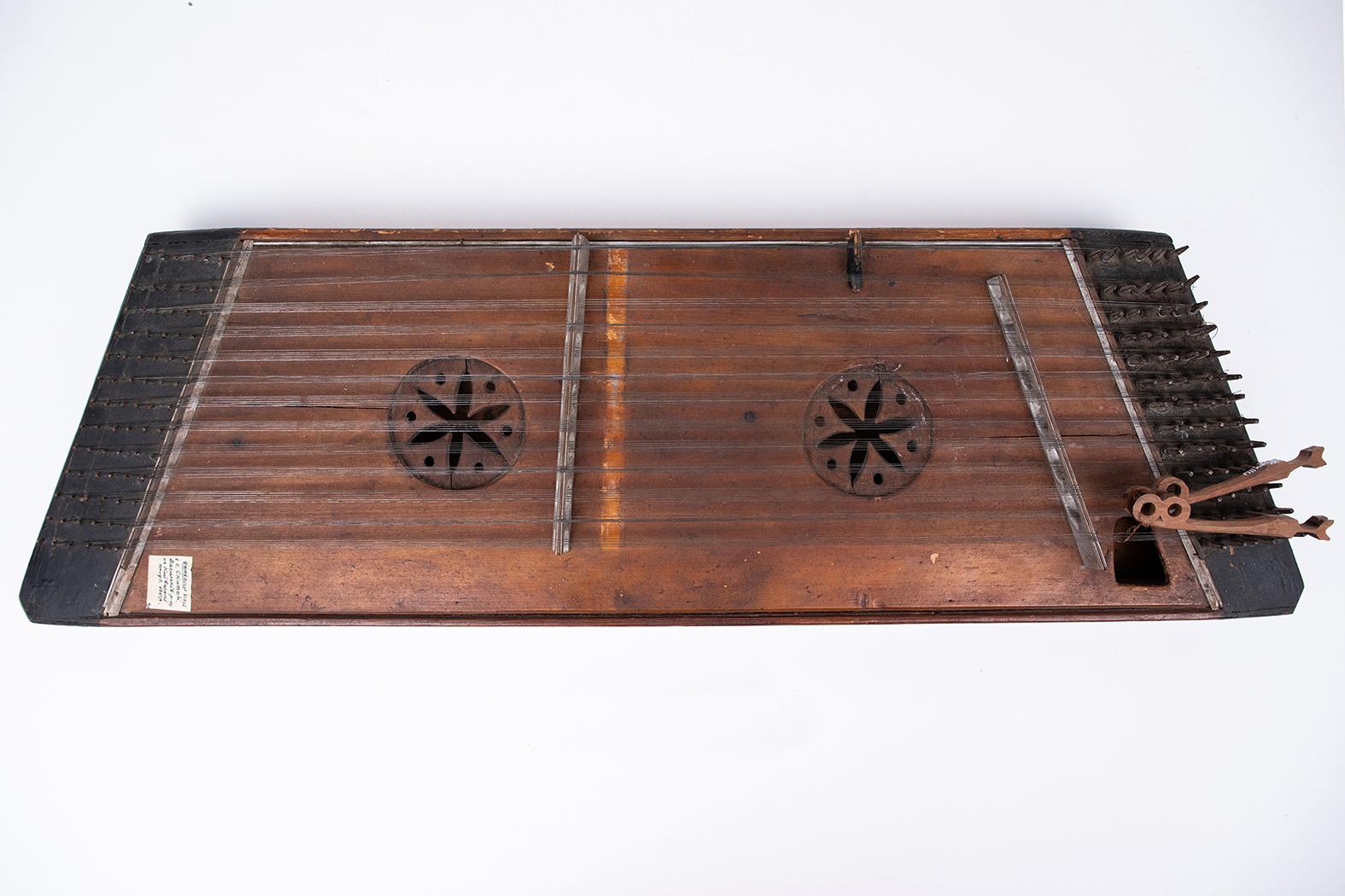 Старовинний струнний музичний інструмент, що має дерев'яний корпус і металеві струни, на яких грають, вдаряючи молоточками або дерев'яними паличками.