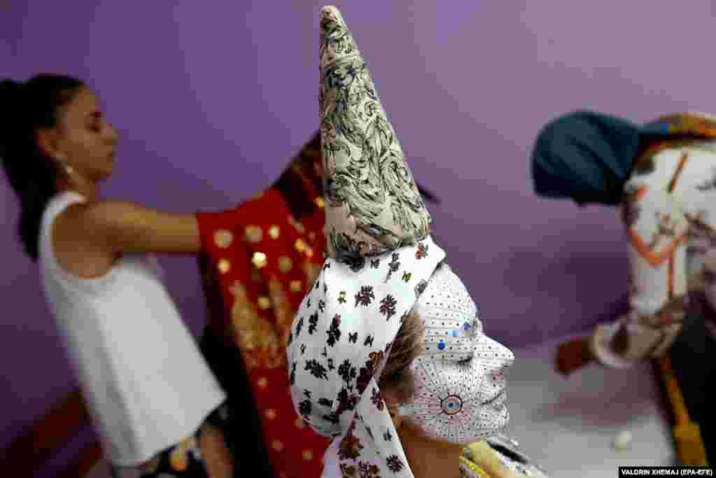 Пред да ја напушти својата куќа, конус се става на главата на невестата и се користи за да се обеси црвен превез преку лицето.