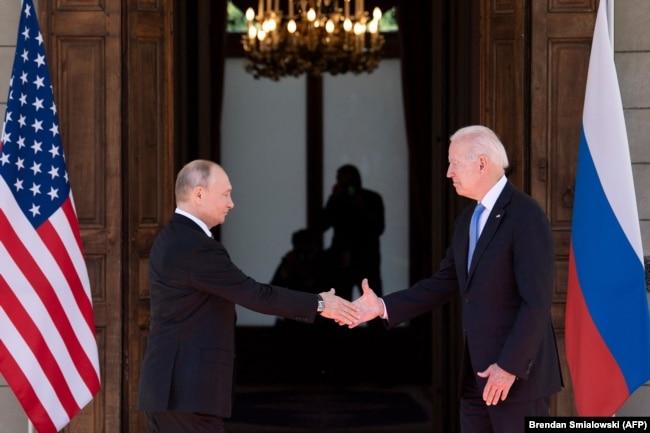 Vladimir Putin shakes hands with U.S. President Joe Biden prior to a summit in Geneva on June 16.