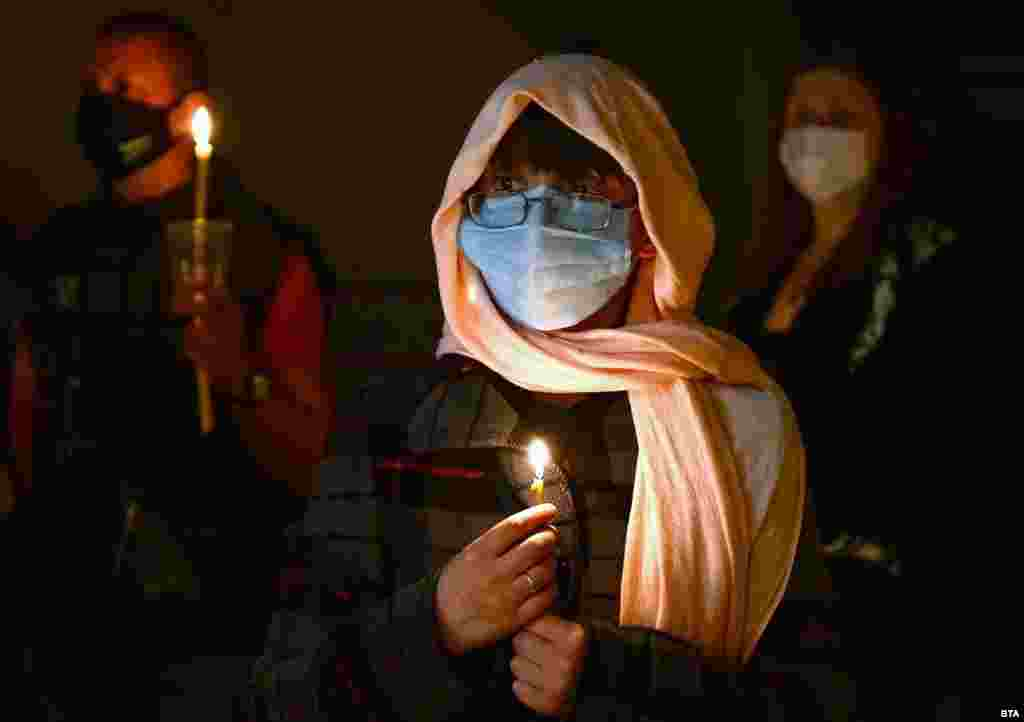 A Bulgarian worshipper wearing a face mask holds a candle during an evening Easter service in the church St. Cyril and Methodius in Isperih.