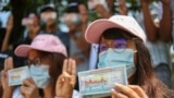 Tüntetők pénzre írt üzenetekkel egy ranguni tiltakozáson a katonai puccs ellen, Mianmarban, 2021. április 15-én