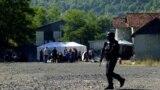 Një pjesëtar i njësive speciale të Policisë së Kosovës ecën pranë disa serbëve, që po protestojnë në Jarinjë më 26 shtator.