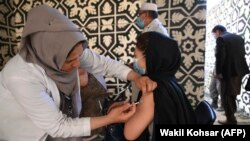 A health worker (left) inoculates a woman with vaccine against COVID-19 at a vaccination center in Kabul in April.