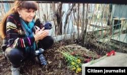 Фотограф Умида Аҳмедова рассом қабри устида қуръон тиловат қилмоқда