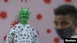 Индиялык жаран COVID-19 илдетин элестеткен тулдун жанында турат. Мумбай (мурдагы Бомбей), Индия. 2020-жылдын 30-декабры.