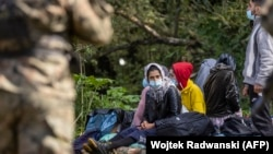 Migrants believed to be from Afghanistan sit on the ground in the small village of Usnarz Gorny near Bialystok, in northeastern Poland, located close to the border with Belarus, on August 20. The migrants have spent more than three weeks trapped in limbo between the two countries.
