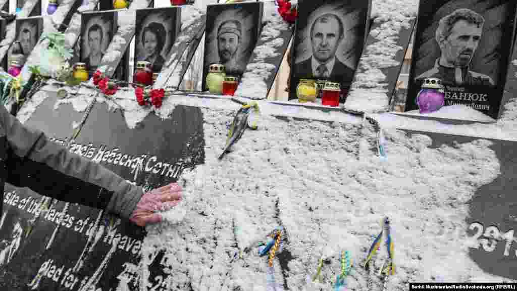 Чоловік струшує сніг ізпортретів загиблих Героїв Небесної сотні