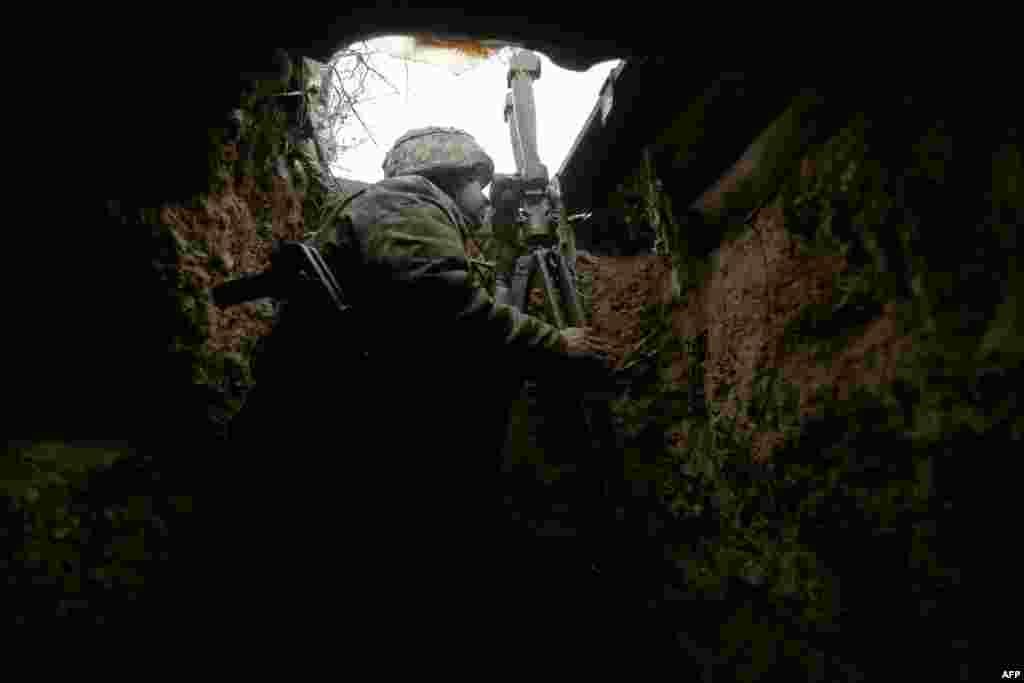 Egy ukrán katona tartja a pozíciójátAvgyijivka közelében, az ukrán katonák és az oroszok által támogatott szakadárok között húzódó frontvonalon.