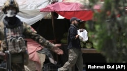 FILE: A security officer carries a baby after gunmen attacked a maternity hospital in Kabul on May 12.