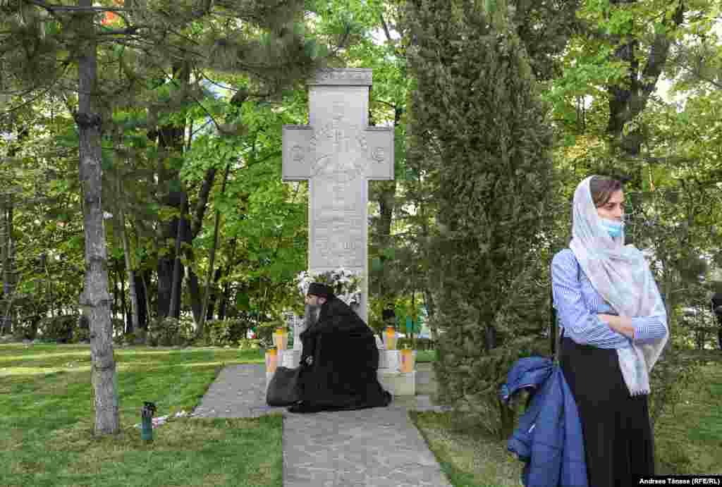 Un călugăr se roagă lângă o cruce în timpul slujbei religioase din Vinerea Mare, la Mănăstirea Radu Vodă din București, România.