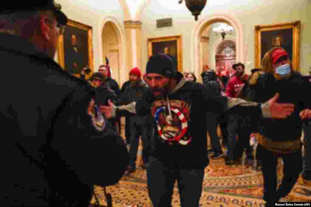 Demonstrant ispred policije u predvorju sale Senata u Vašingtonu
