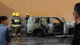 Tűzoltók dolgoznak egy kiégett autó körül, amely egy rakétatámadásban gyulladt ki Hegyi-Karabahban.