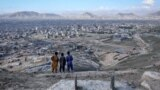 Afghan children look over Kabul as they stand near the grave of a girl who lost her life in the recent attack on a school. (epa-EFE/Hedayatullah Amid)