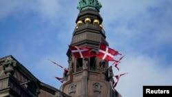 Prema danskom zakonu optuženi, koji nije identifikovan, nije mu naveden ni pol, ni starost ni profesija, može da dobije šest godina zatvora. ( Foto: zastave Danske na dvorcu Christiansborg u Kopenhagenu)