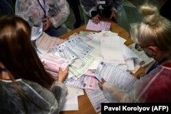 A helyi választási bizottság tagjai kiürítik az urnákat és szétválogatják a szavazólapokat a további számláláshoz vasárnap, a háromnapos parlamenti választás első napján a távol-keleti Vlagyivosztokban, 2021. szeptember 17-én