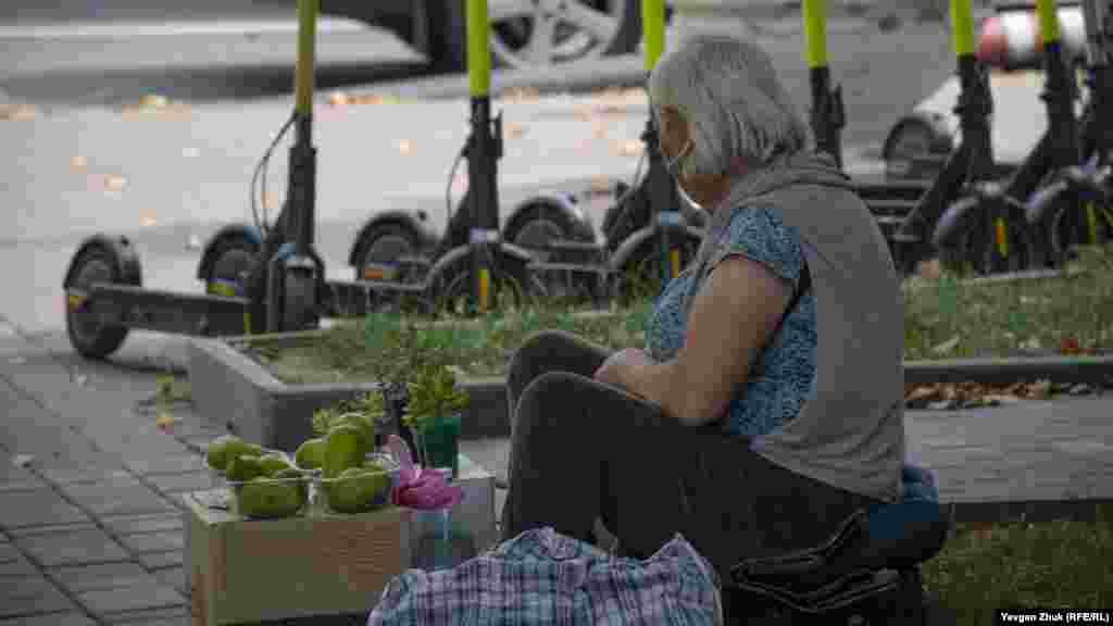 На бульваре под сенью деревьев женщина продает инжир