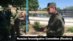Investigators work at the site of the accident at the sewage plant in the village of Dmitriadovka outside Taganrog.