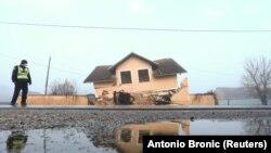 Policajac posmatra teško oštećenu kuću u selu Prokopa, u središnjoj Hrvatskoj nakon razornog zemljotresa 29. prosinca 2020.