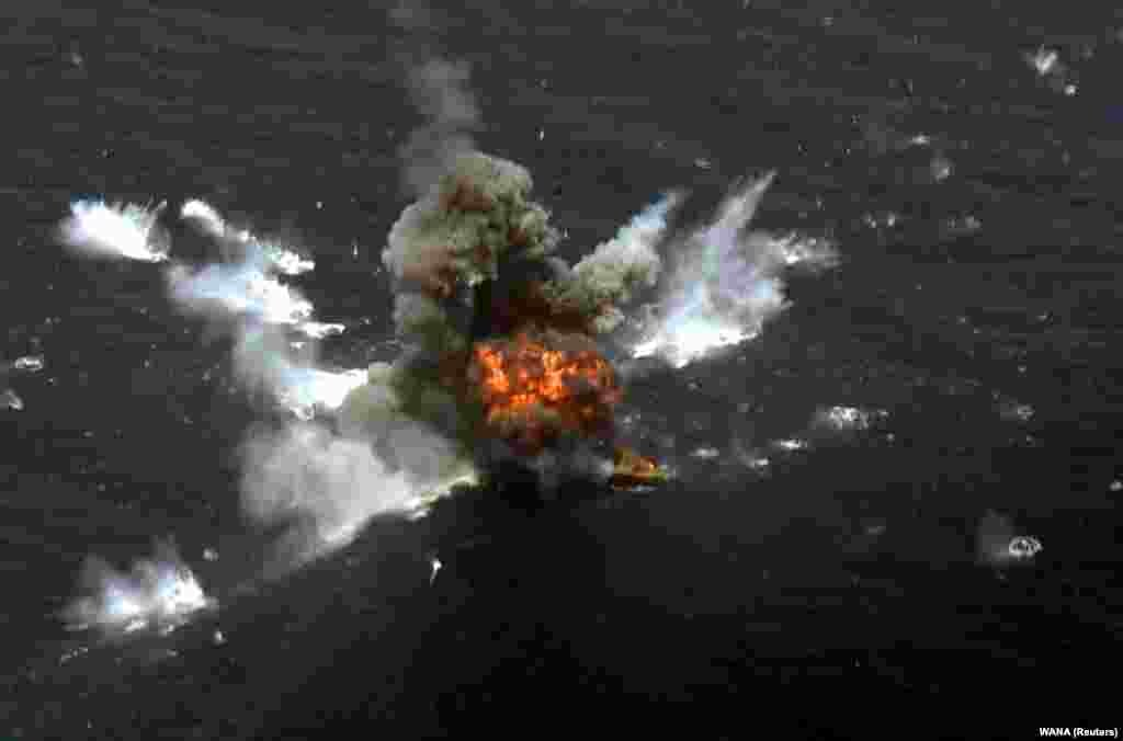 An explosion is seen after a new Iranian-made cruise missile was fired during war games in the northern Indian Ocean, near the entrance to the Gulf, on June 17. (WANA via Reuters)