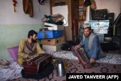 2021. június 8. Szajed Mohammad hivatásos zenész (jobb oldalt) Gulam Mohammad harmóniumjátékossal gyakorol dzsapánival, egy hagyományos közép-ázsiai húros hangszerrel a kandahári zenei stúdióban. A tálibok 1996–2001-es uralmuk alatt több tucat ártatlannak tűnő tevékenységet és időtöltést tiltottak be Afganisztánban – köztük a sárkányeregetést, a televíziós szappanoperákat, a galambversenyeket, a frizurákat és még a zenélést is. Az azóta eltelt években e tevékenységek visszatértek, de 2021 nyarán egyre nagyobb volt a félelem, hogy ismét betiltják őket, ha a keményvonalas iszlamisták visszatérnek a hatalomba