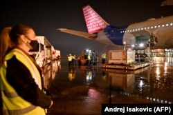 Workers unload containers holding 500,000 doses of China's Sinopharm vaccine from a special Air Serbia flight at Belgrade's airport on February 10.