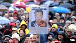"""Employees of Hungarian radio station Klubradio and their supporters hold umbrellas and a poster with a photo of Hungarian Prime Minister Viktor Orban reading, """"Don't you see that you bit off more than you can chew?"""" at a demonstration for the freedom of speech in Budapest on February 24, 2013"""